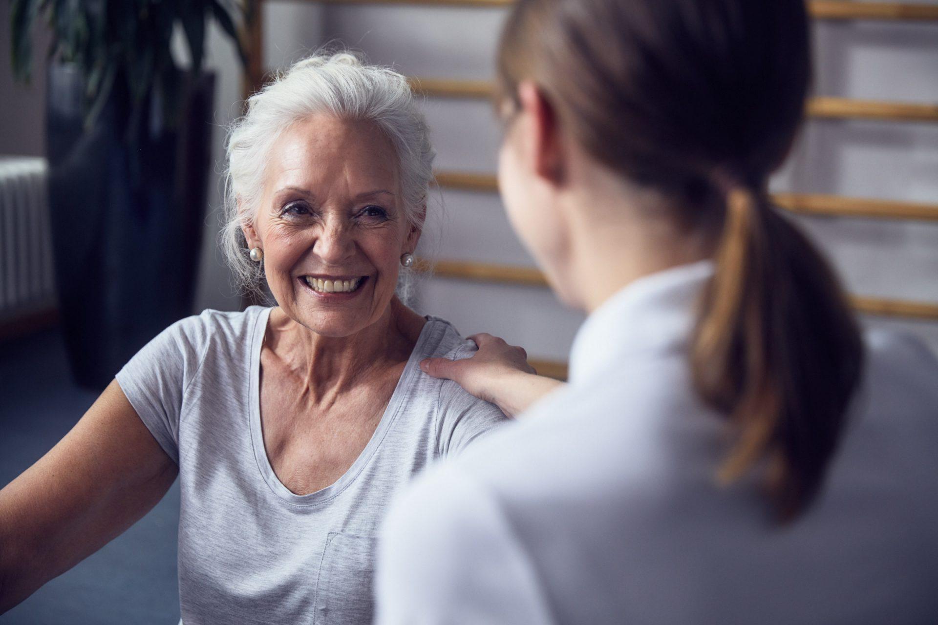 erfreute Seniorin mit ihrer Pflegefachkraft