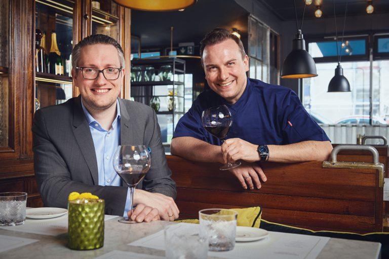 Sternekoch Tim Raue mit einem Freund beim Wein trinken in der Brasserie Colette