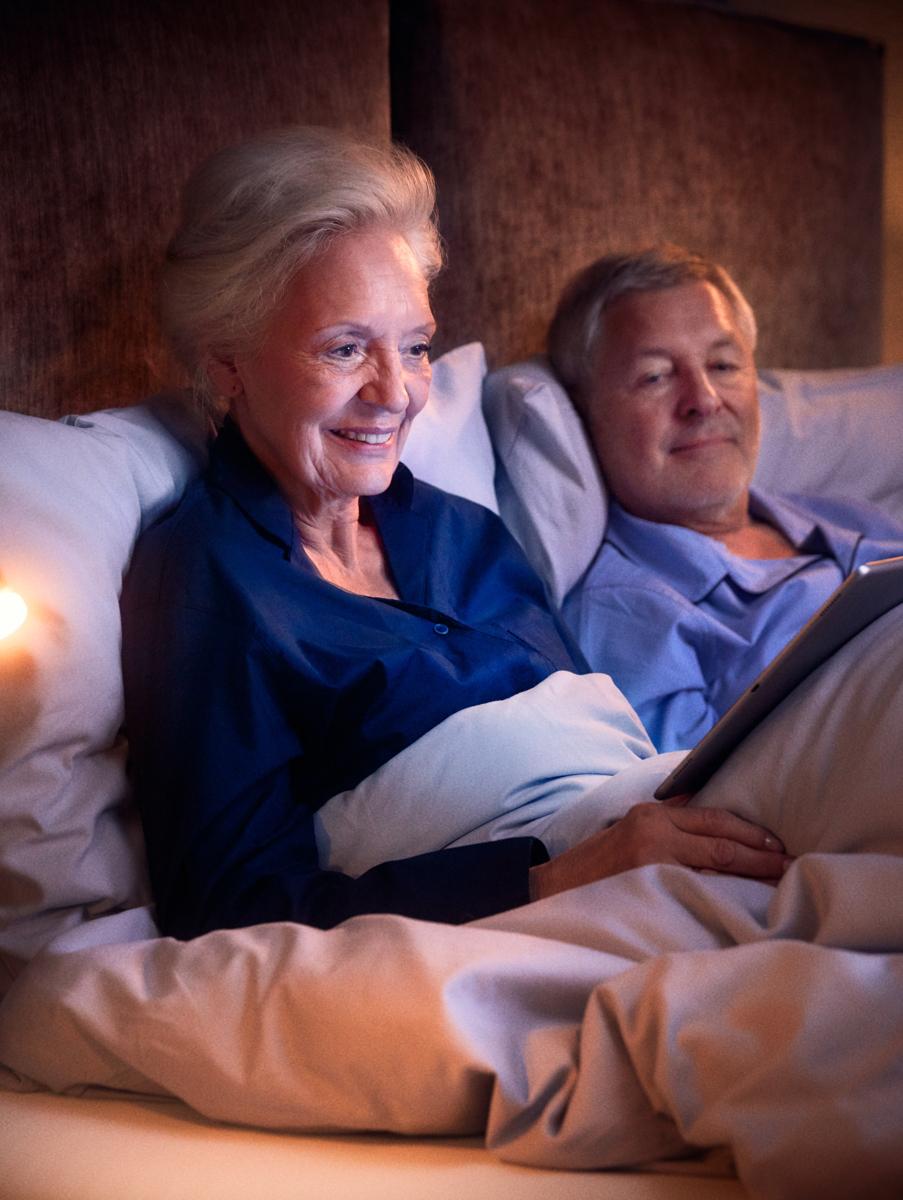Ein älteres Ehepaar im Bett ihrer Wohnung in der Tertianum Residenz