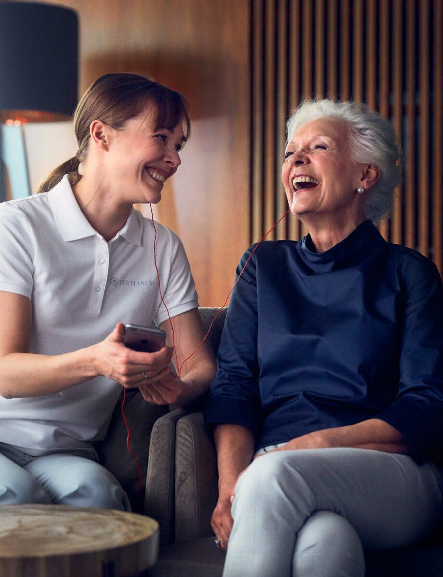 Lachende Seniorin mit Pflegehelferin im Altersruhesitz Tertianum