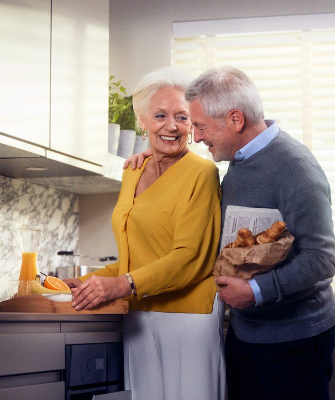 Zwei glückliche Senioren in der Küche ihrer Seniorenwohnung in der Tertianum Residenz