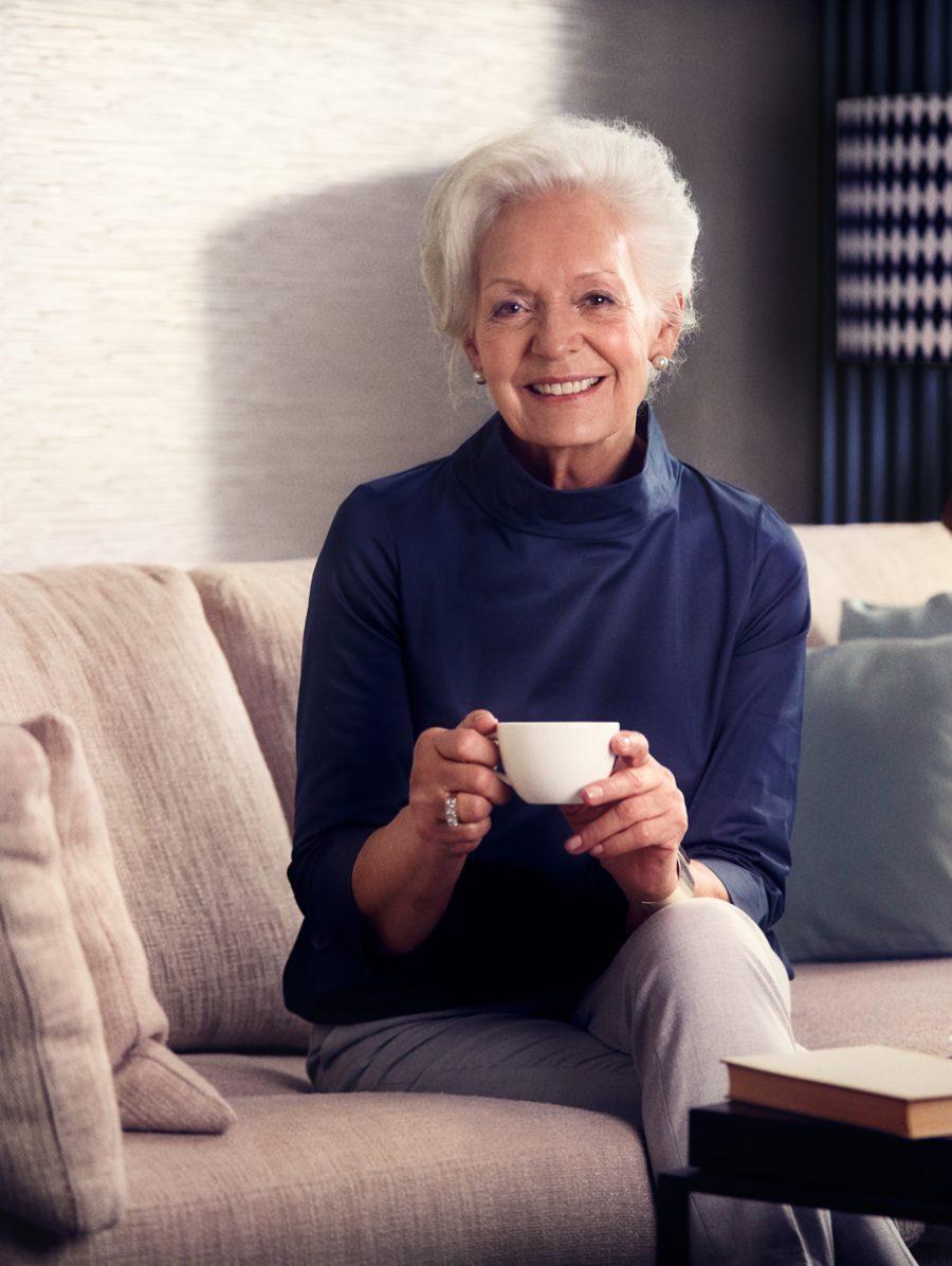 Eine lächelnde Senioren beim Kaffee trinken in ihrer Tertianum Residenzwohnung