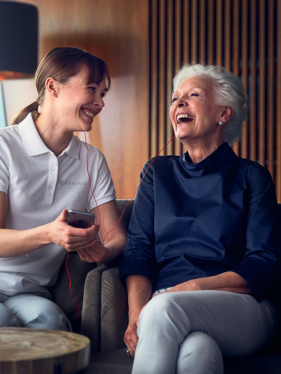 Eine ältere Dame lachend im Gespräch mit einer Pflegekraft
