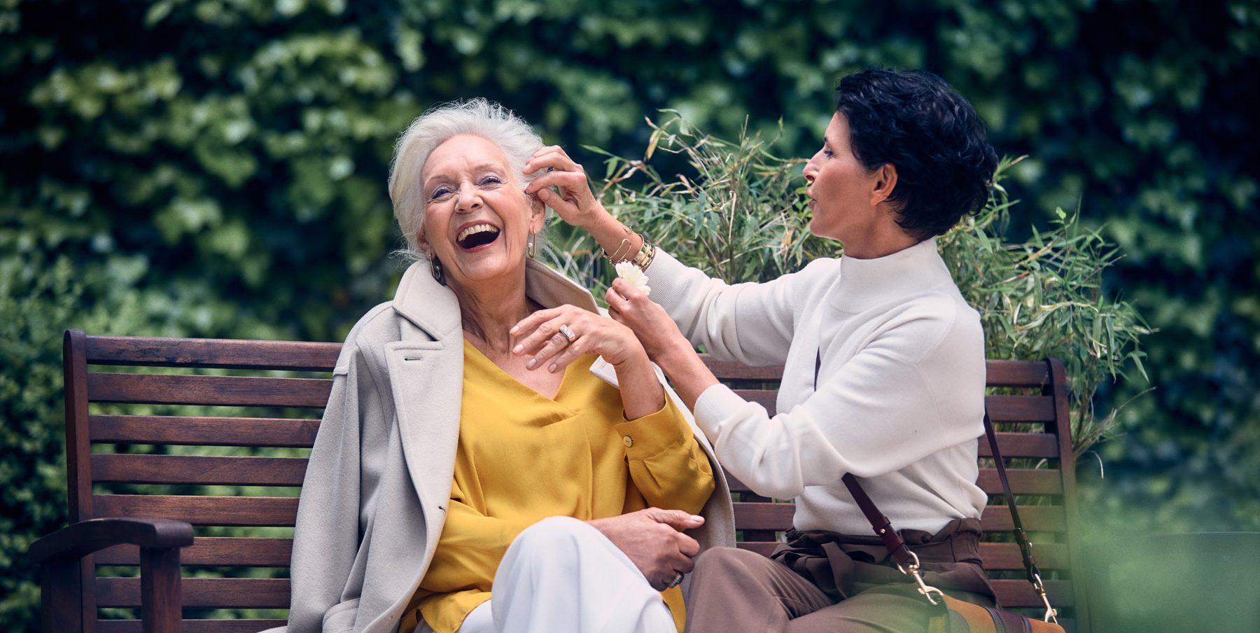 Zwei ältere Frauen die gemeinsam auf einer Parkbank sitzen und lachen