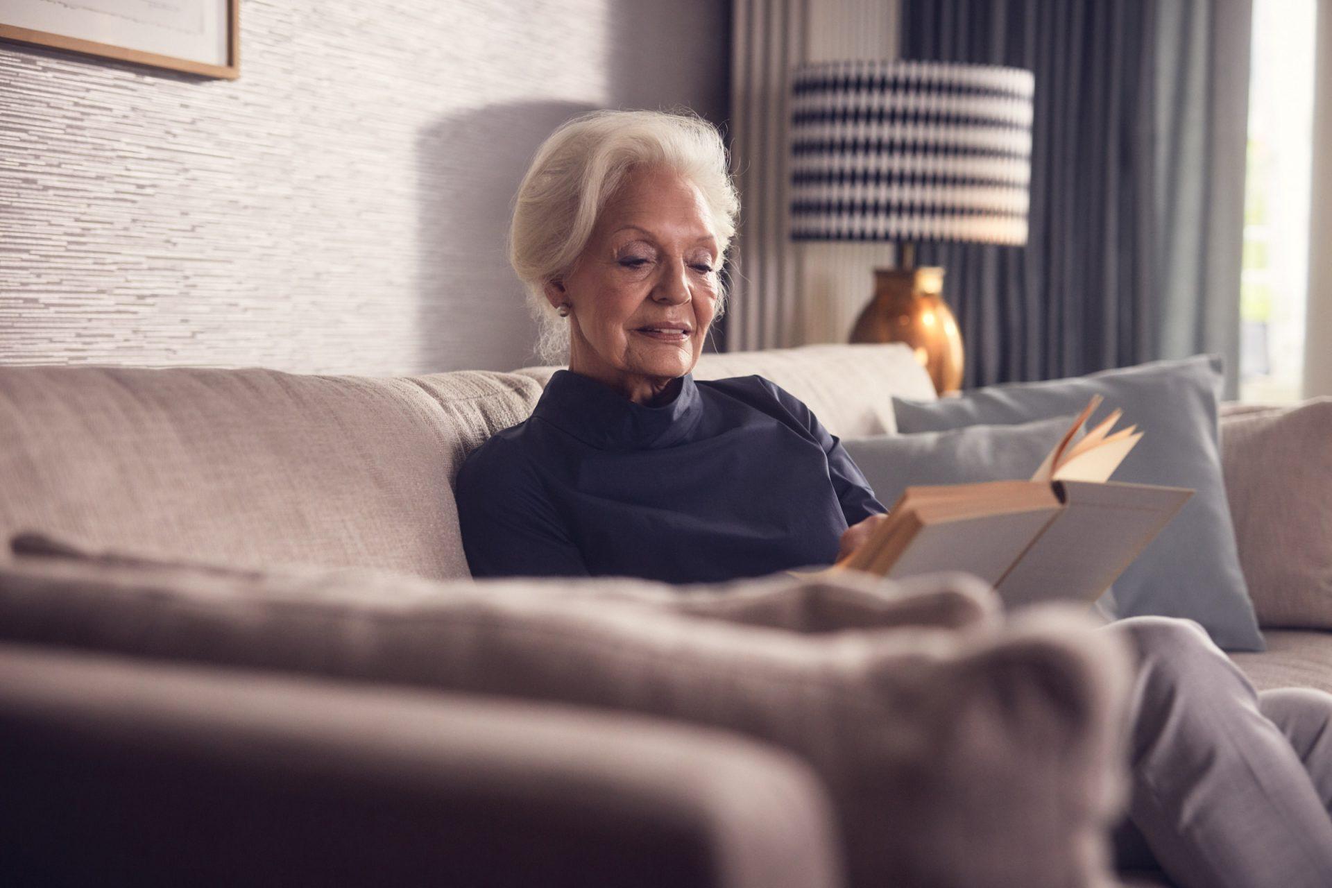 Eine ältere Dame beim Lesen in ihrer Seniorenwohnung